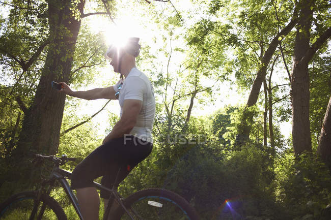 Cyclist stopping for break in forest in backlit — Stock Photo