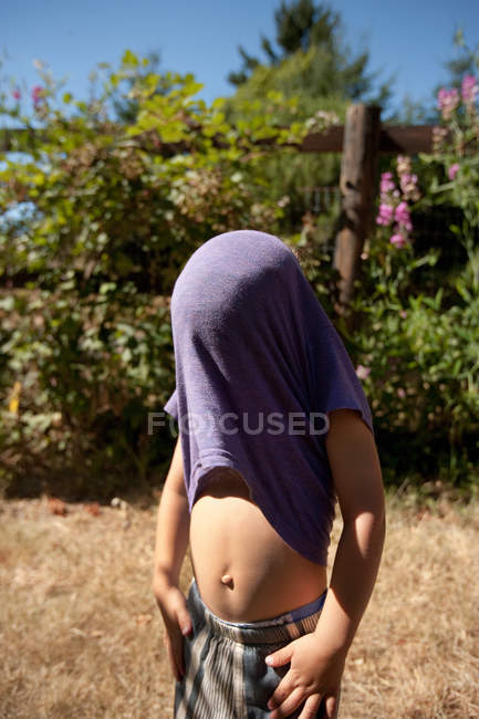 Boy with t shirt stuck on head in field — Stock Photo