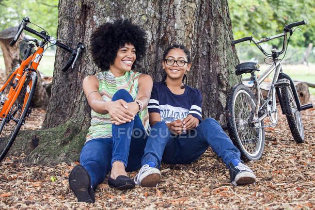Portrait de femme mature et fils assis contre un arbre du parc — Photo de stock
