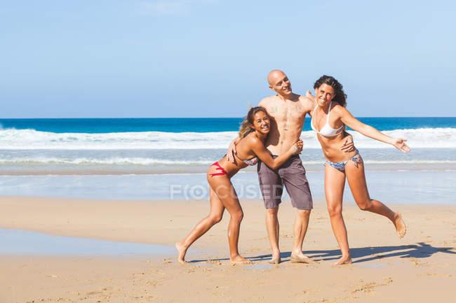 Retrato de homem e duas jovens mulheres vestindo roupa de banho na praia, El Cotillo, Fuerteventura, Espanha — Fotografia de Stock