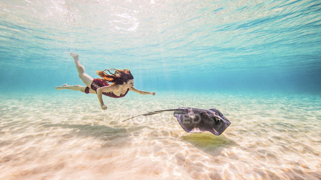 Female free diver swimming with stingray on seabed — стоковое фото