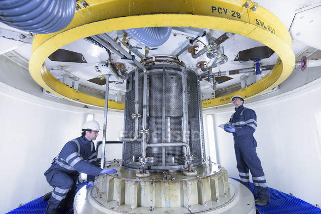 Workers inspecting turbine housing in hydroelectric power station — Stock Photo