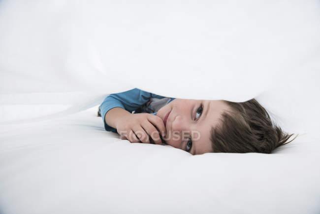 Junge liegt zwischen weißen Bettlaken — Stockfoto