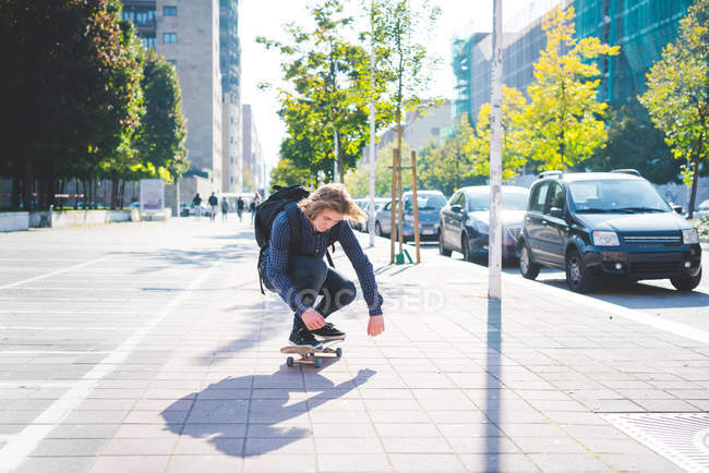 Young male skateboarder crouching whilst skateboarding on sidewalk — Stock Photo