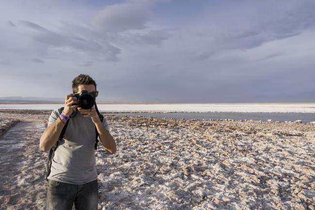 Фотограф человек с камерой, делающий снимки в Сан-Педро-де-Атакама — стоковое фото
