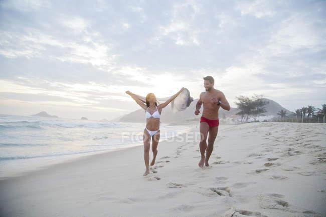 Mid adult couple running along beach in swimwear — Stock Photo