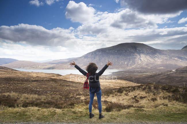 Mujer adulta en las montañas con los brazos en alto, Isla de Skye, Hébridas, Escocia - foto de stock