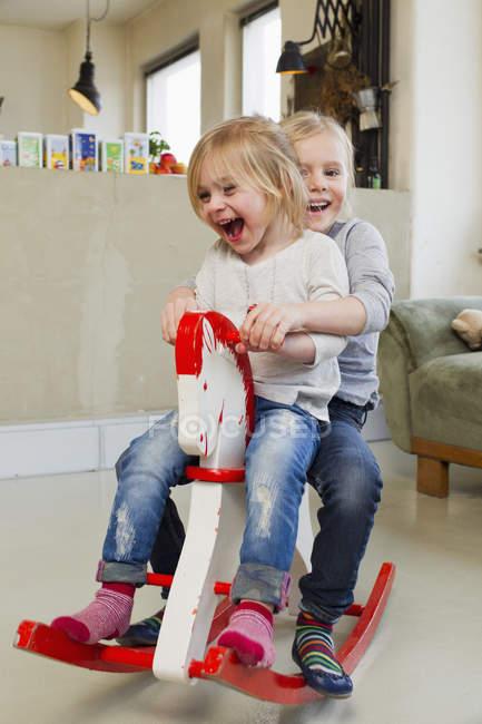 Две сестры дошкольника, играющие на лошади-качалке — стоковое фото