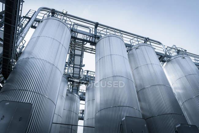 Vista de ángulo bajo de tanques y tuberías en planta de mezcla de aceite, Amberes, Bélgica, Europa - foto de stock