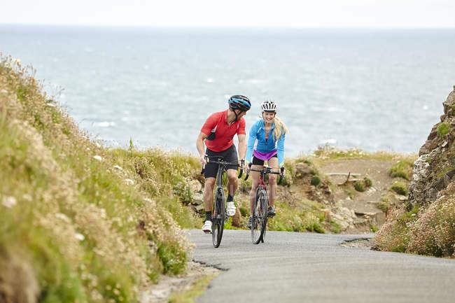 Велогонщики едут по дороге с видом на океан — стоковое фото