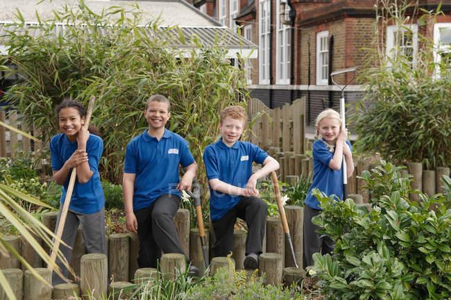 Portrait of four schoolchildren with gardening tools in garden — Stock Photo