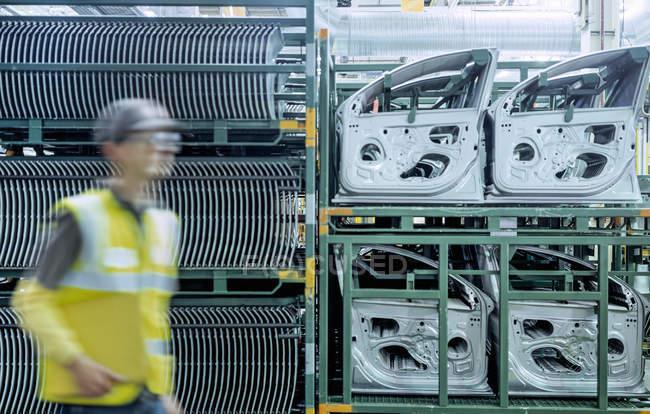 Рабочий, проходящий мимо автомобильных дверей на автомобильном заводе — стоковое фото