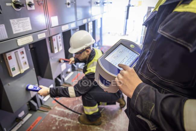 Trabalhadores que usam a unidade parcial da descarga na subestação da eletricidade — Fotografia de Stock