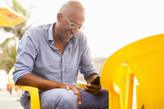 Reifer Mann liest Smartphone-Texte in Bar am Strand von Ipanema, Rio de Janeiro, Brasilien — Stockfoto