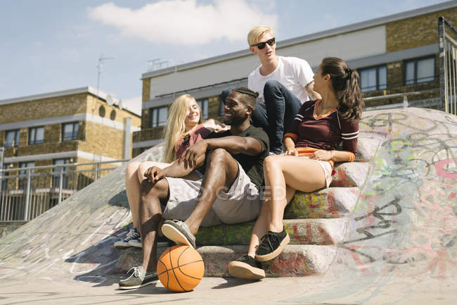 Four male and female basketball friends sitting chatting in city skatepark — Stock Photo