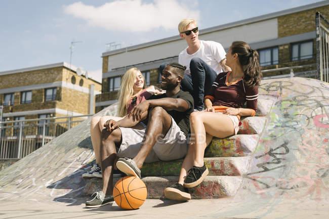 Quatre amis de basket-ball masculin et féminin assis bavardant au skatepark de la ville — Photo de stock