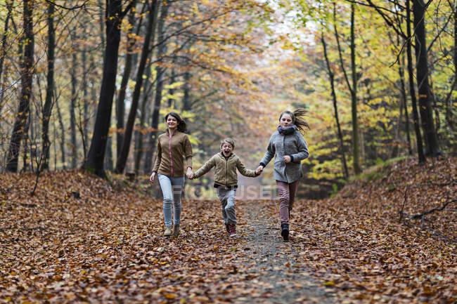 Girls running in autumn forest — Stock Photo