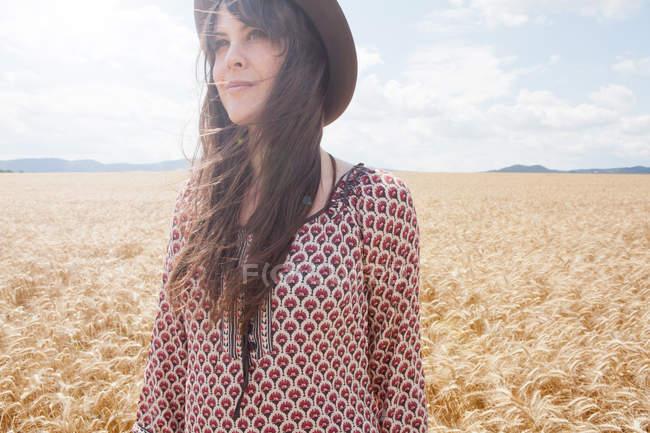 Mitte erwachsene Frau steht im Weizenfeld — Stockfoto
