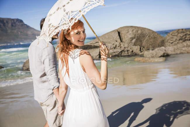Casal de mãos dadas, andando na costa segurando guarda-chuva olhando sobre o ombro na câmera sorrindo — Fotografia de Stock