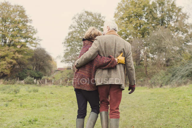 Couple in garden with arms around each other, rear view — Stock Photo