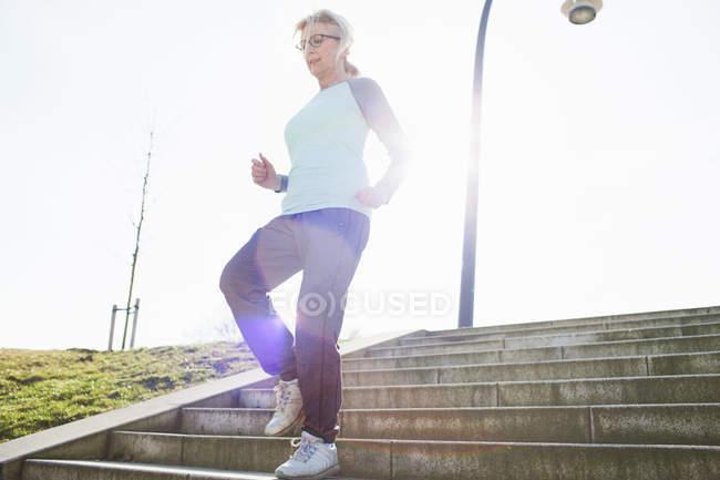 Зрелая женщина бежит по ступенькам — стоковое фото