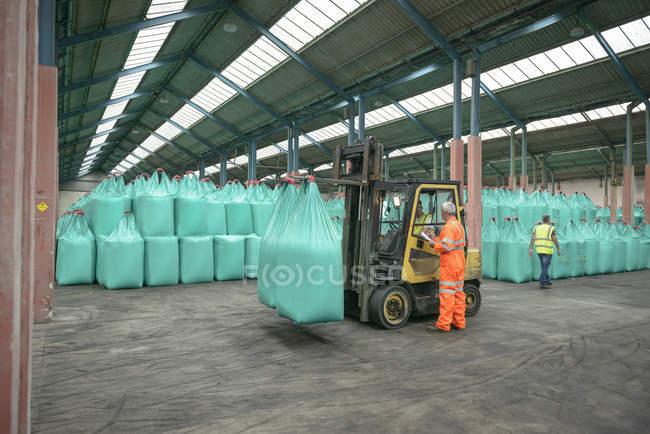 Travailleurs et fourche élévateur en magasin engrais en vrac dans le port — Photo de stock