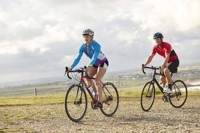 Ciclistas montando na estrada de cascalho no dia ensolarado — Fotografia de Stock