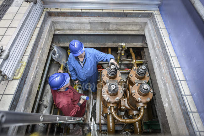 Engineers inspecting electrical unit during power station outage, elevated view — Stock Photo