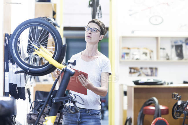 Woman in bicycle workshop holding clipboard checking bicycle — Stock Photo