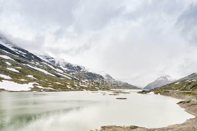 White lake and snowcapped mountains under cloudy sky — Stock Photo
