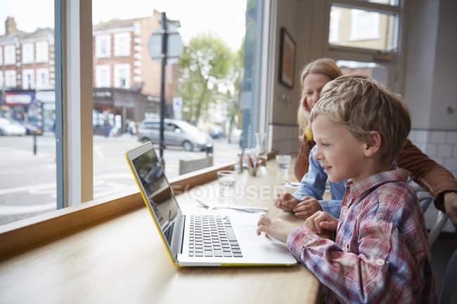 Bambino che utilizza il computer portatile in cafe, London, UK — Foto stock