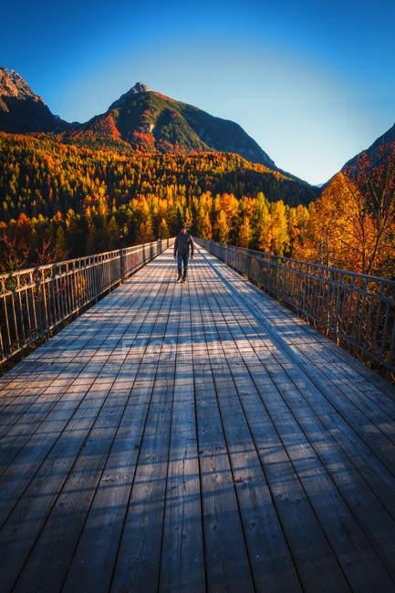 Uomo che attraversa il ponte di legno, Scuol, Engadina, Svizzera — Foto stock
