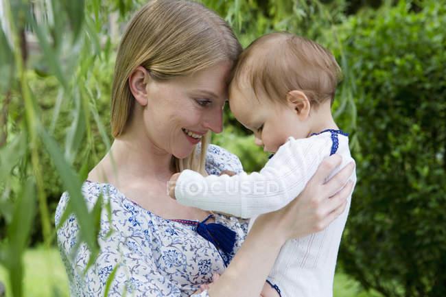 Mère et bébé fille face à face dans le jardin — Photo de stock