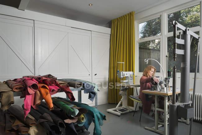 Mujer en la máquina de coser en el taller - foto de stock