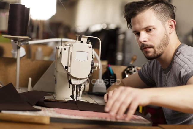 Homem usando máquina de costura para costurar couro em fabricantes de jaqueta de couro — Fotografia de Stock