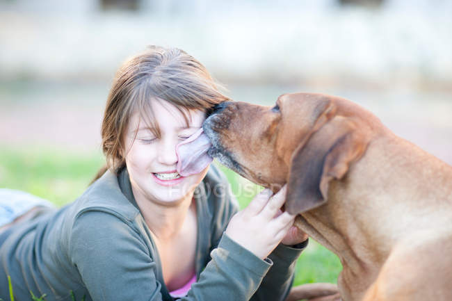 Portrait of Dog licking girl's face — Stock Photo