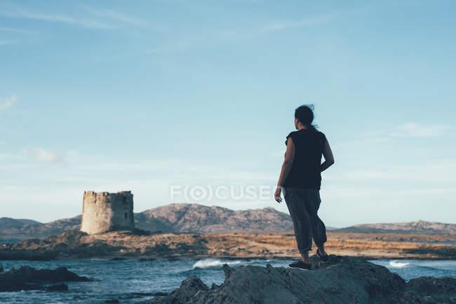 Rear view of woman on rocks looking across sea at derelict lighthouse, Stintino, Sassari, Italy — Stock Photo