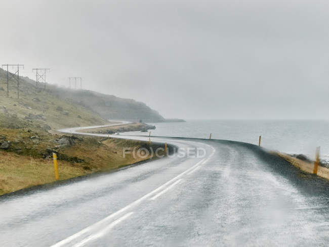 Scenic view of Wet winding coastal road, Hof, Iceland — Stock Photo