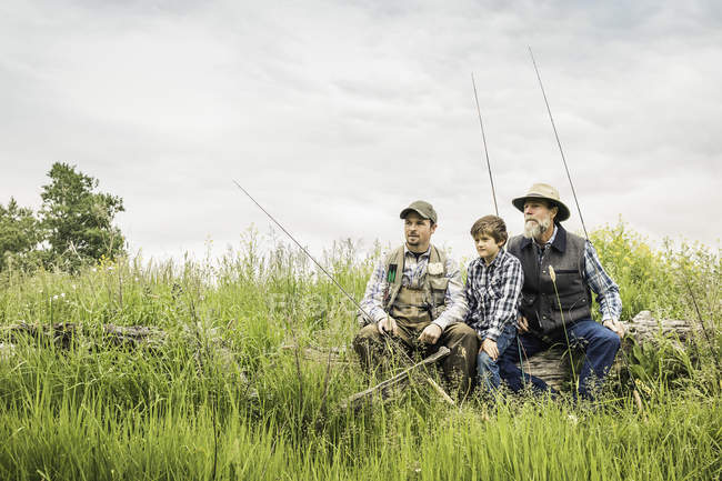 Multi generation family holding fishing rods sitting on log in field looking away — Stock Photo