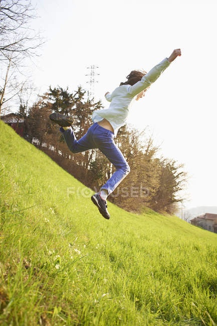 Young boy jumping down steep grassy field — Stock Photo