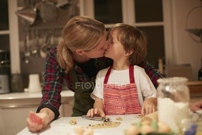 Женщина целует сына во время выпечки на кухне счетчик — стоковое фото