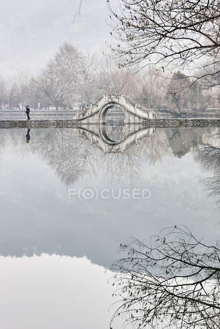 Mirror image of bare trees and footbridge over lake, Hongcun Village, Anhui Province, China — Stock Photo