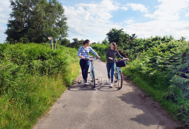 Two young adults pushing bicycles along country lane — Stock Photo