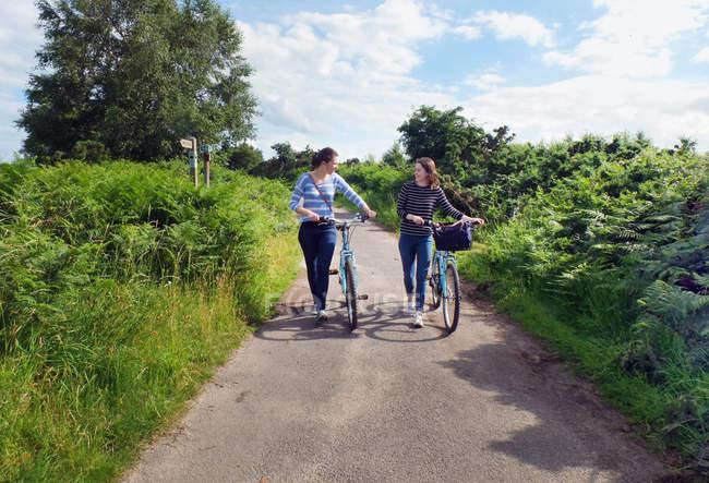 Deux jeunes adultes poussant des vélos le long de la voie de campagne — Photo de stock