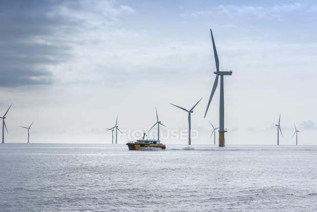 Вид на оффшорную ветряную ферму и служебную лодку — стоковое фото