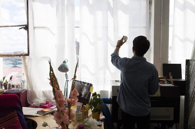 Traseira em silhueta vista masculino segurando imprimir a janela iluminada pelo sol em estúdio de impressão — Fotografia de Stock
