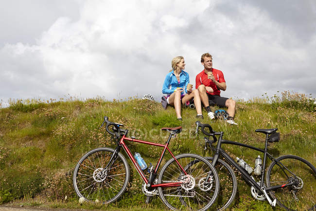 Ciclisti che si rilassano e chiacchierano su una collina erbosa — Foto stock
