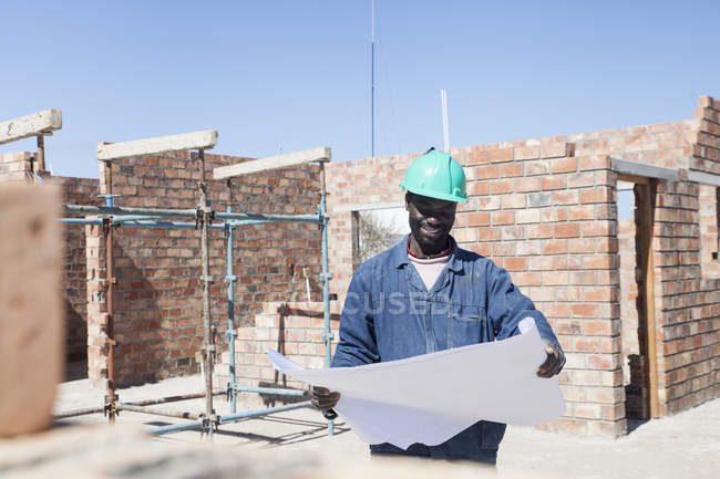 Builder looking at blueprint on construction site — Stock Photo