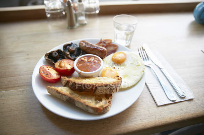 Breakfast plate of fried eggs, sausages, mushrooms, tomatoes and toasts — Stock Photo