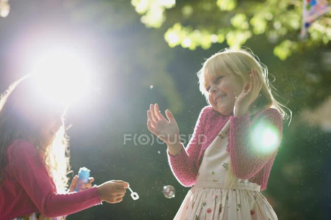 Due ragazze che soffiano e fanno scoppiare bolle nel giardino illuminato dal sole — Foto stock